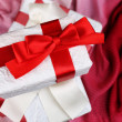 Beautiful gifts with red ribbons on pink cloth — Stock Photo