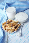 Homemade yogurt and tasty sweet bread sticks on wooden table background — Stock Photo
