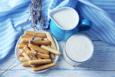 Homemade yogurt in jug and tasty sweet bread sticks on wooden table background — Stock Photo