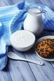 Homemade yogurt and tasty cookies on wooden table background — Stock Photo