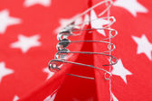 Safety pins on fabric background — Stock Photo
