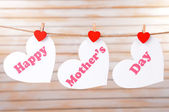 Happy Mothers Day message written on paper hearts on light background — Foto Stock