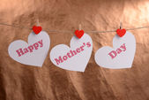 Happy Mothers Day message written on paper hearts on brown background — Stock Photo
