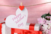 Happy Mothers Day message written on paper heart with flowers on pink background — Foto Stock