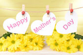 Happy Mothers Day message written on paper hearts with flowers on yellow background — Stock Photo