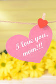 Happy Mothers Day message written on paper heart with flowers on yellow background — Stock Photo