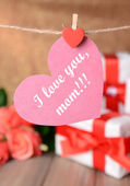 Happy Mothers Day message written on paper heart with flowers on brown background — Stock Photo