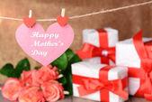 Mensaje del día de las madres feliz escrito en papel corazón con flores sobre fondo marrón — Foto de Stock