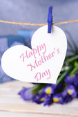 Happy Mothers Day message written on paper heart with flowers on purple background — Stock Photo
