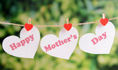 Happy Mothers Day message written on paper hearts with flowers on bright background — Stock Photo