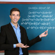 Teacher explaining formulas written on blackboard to pupils — Stock Photo