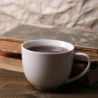 Cup of hot tea with books on table on paper background — Stock Photo #43664555