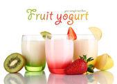 Deliciosos iogurtes com frutas em copos isolados no branco — Foto Stock