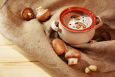 Mushroom soup in pot,on napkin,  on wooden background — Stock Photo