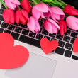 Red hearts and flowers on computer keyboard close up — Stock Photo #43722795