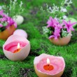 Conceptual Easter composition. Burning candle in egg and flowers on green grass background, close-up — Stock Photo #43723783