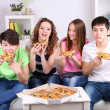 Group of young friends eating pizza in living-room on sofa — Stock Photo #43726573