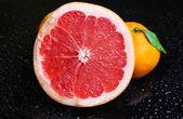 Ripe sweet tangerine and grapefruit, on dark color background — Stock Photo