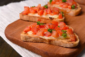 Delicious bruschetta with tomatoes on cutting board close-up — Stockfoto