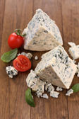 Tasty blue cheese with basil and tomato, on wooden table — Stock Photo