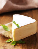 Tasty Camembert cheese with basil, on wooden table — Stock Photo