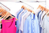 Different clothes on hangers, on gray background — Stok fotoğraf