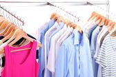 Des vêtements différents sur des cintres, sur fond gris — Photo