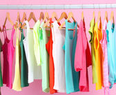 Different clothes on hangers, on pink background — 图库照片