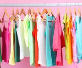 Des vêtements différents sur des cintres, sur fond rose — Photo