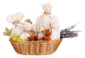 Textile sachet pouches with dried flowers, herbs  and berries  in wicker basket, isolated on white — Stock Photo