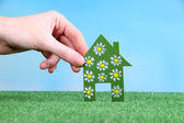Little paper house in hand on green grass on bright background — Stock Photo