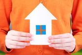 Little paper house in hand close-up, on bright background — Foto Stock