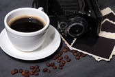 Coffee cup, vintage camera and old blank photos, on wooden background — Stock Photo