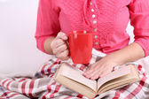 Woman sitting on sofa,  reading book and  drink coffee or tea, close-up — Stock Photo