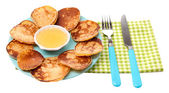 Fried pancakes on color plate, on color napkin, isolated on white — Stock Photo