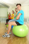 Young beautiful peoples engaged with balls in gym — Stok fotoğraf