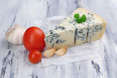 Tasty blue cheese on old wooden table — Stockfoto