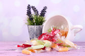 Tasty candies in mug with flowers on table on bright background — Stock Photo