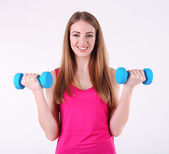 Young beautiful fitness girl exercising with dumbbells in gym — Stock Photo