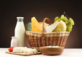 Basket with tasty dairy products on wooden table, on dark brown background — Stock Photo