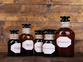 Historic old pharmacy bottles with label   on wooden background — Stock Photo