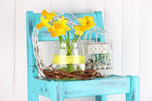 Beautiful flowers in wicker basket, on color fabric and  wooden background — Stock Photo