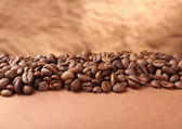 Coffee beans on table on brown background — Stock Photo