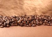 Kaffebönor på bordet på brun bakgrund — Stockfoto