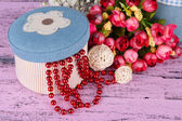 Decorative box with beads and flowers on wooden background — Stock Photo