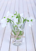 Beautiful bouquets of snowdrops in vases on wooden background — Stock Photo