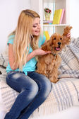 Beautiful young woman with cocker spaniel on couch in room — Foto Stock