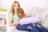 Beautiful young woman with cocker spaniel on couch in room — ストック写真