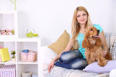 Beautiful young woman with cocker spaniel on couch in room — 图库照片
