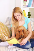 Beautiful young woman with cocker spaniel on couch in room — Photo